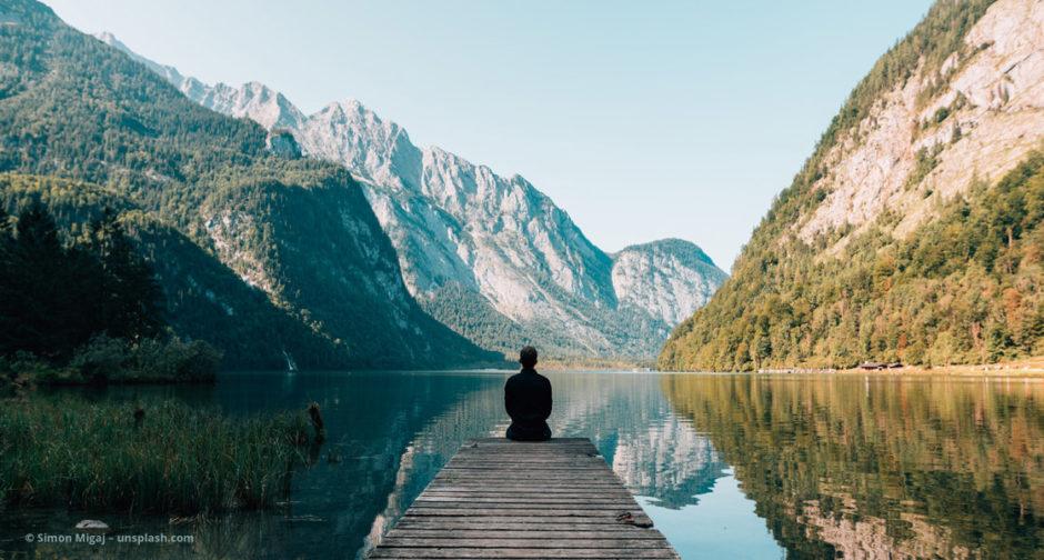 Mann sitzt auf einem Steg am See © Simon Migaj – unsplash.com